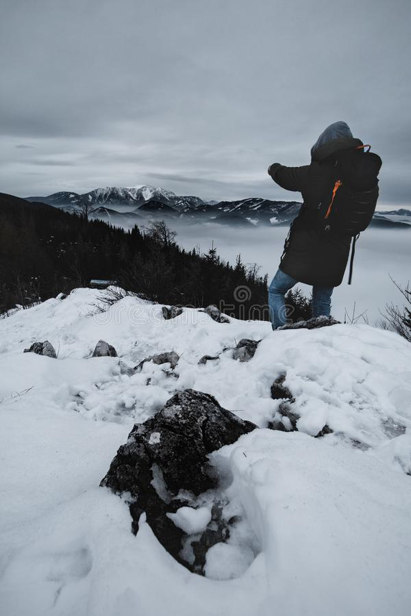 Hiker is standing on a mountain peak in winter. In lower austria stock photography