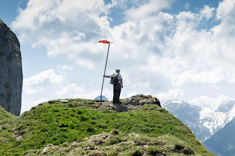Hiker standing next to the wind vane and looking down to the val. Ley stock photos