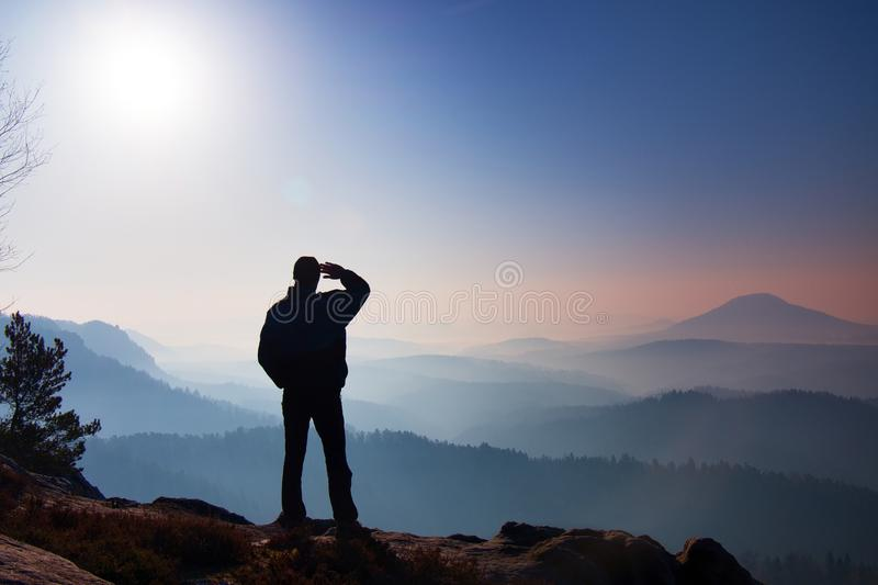 Hiker is standing on the peak of rock in rock empires park and watching over the misty and foggy morning valley to Sun royalty free stock photography