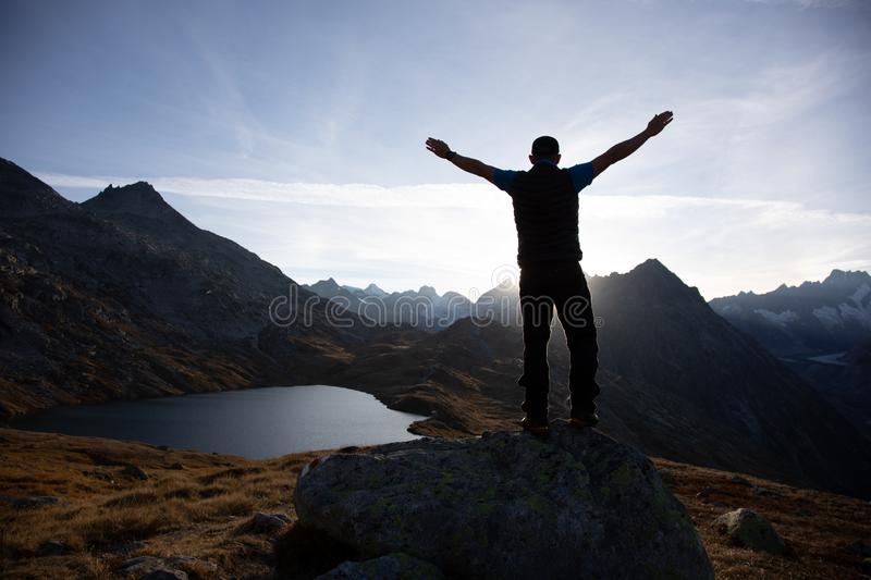 Hiker is standing on a rock with raised hands and enjoying sunrise in the Alps in Switzerland royalty free stock image