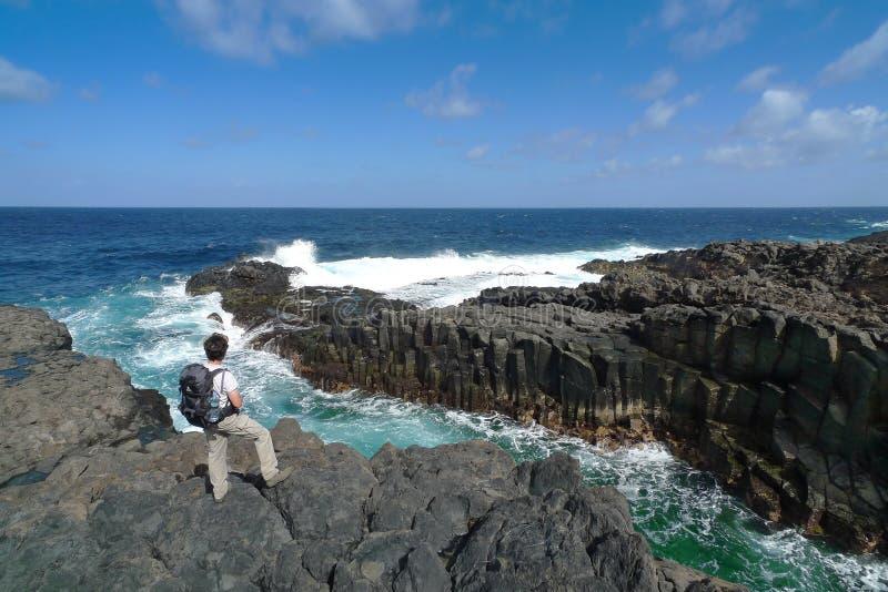 Hiker is standing on the rocky coast of El Hierro stock image