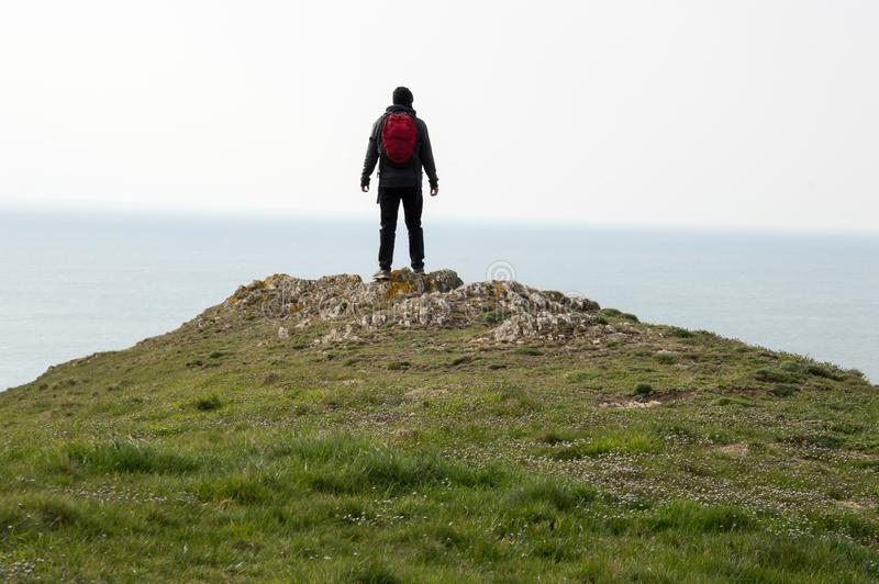 A hiker standing on top of a hill, looking out to sea, Baggy Point, Devon, UK.  royalty free stock images