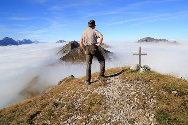 Hiker is standing on the top of a mountain. With clouds in background royalty free stock photo