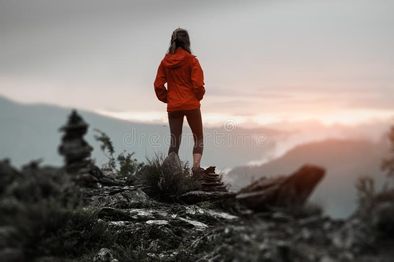 Young woman near cairns. Hiker stands on the cliff and enjoys sunset surrounded by rocks and stacked stones. Altai Republic, Russia royalty free stock photo