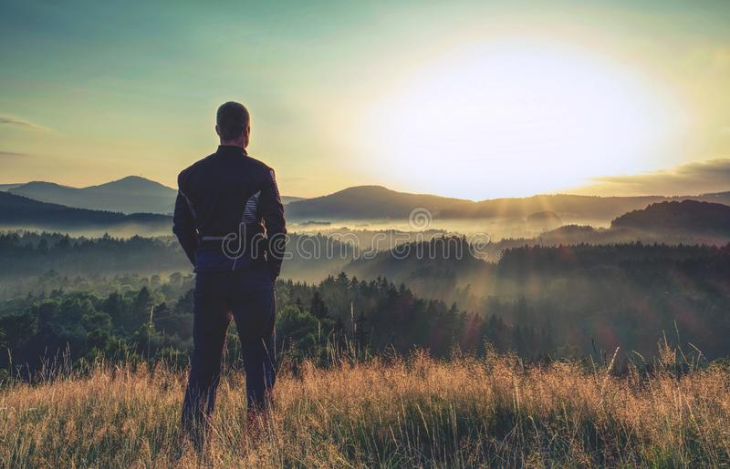 Hiker stands and enjoys valley view from hill stock photos