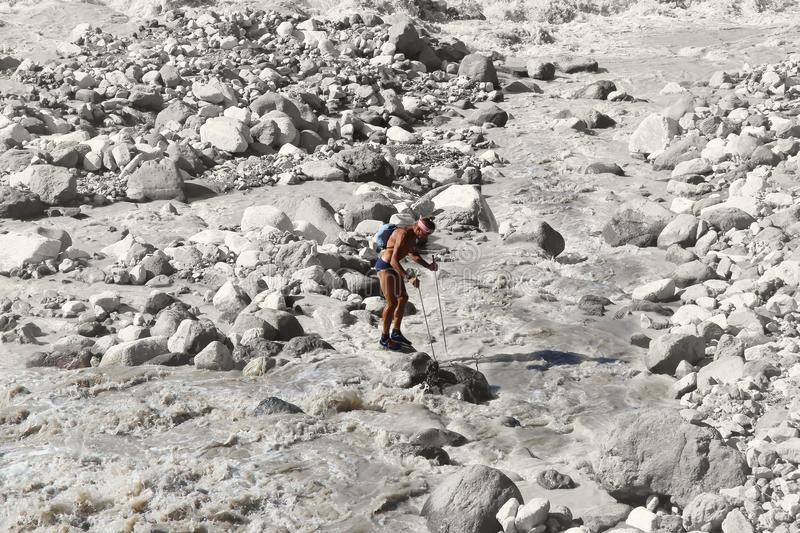 Hiker stands on a rock in the midst of a raging mountain river royalty free stock images