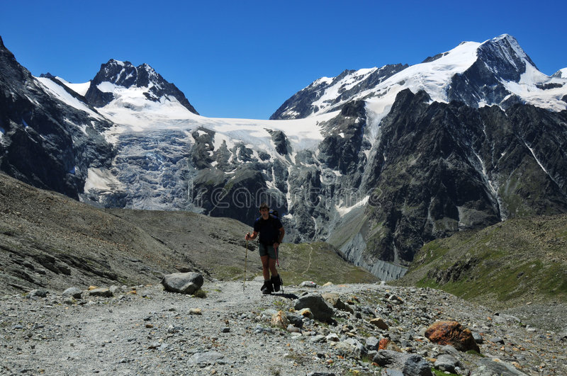Hiker in Swiss Alps. A hiker equiped for glacier walking in the Swiss Alps near 3000m altitude. In the background the Pigne d'Arolla on the right, and the lower stock photography
