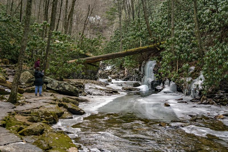Hiker Taking a Photo of Frozen Stony Creek stock images