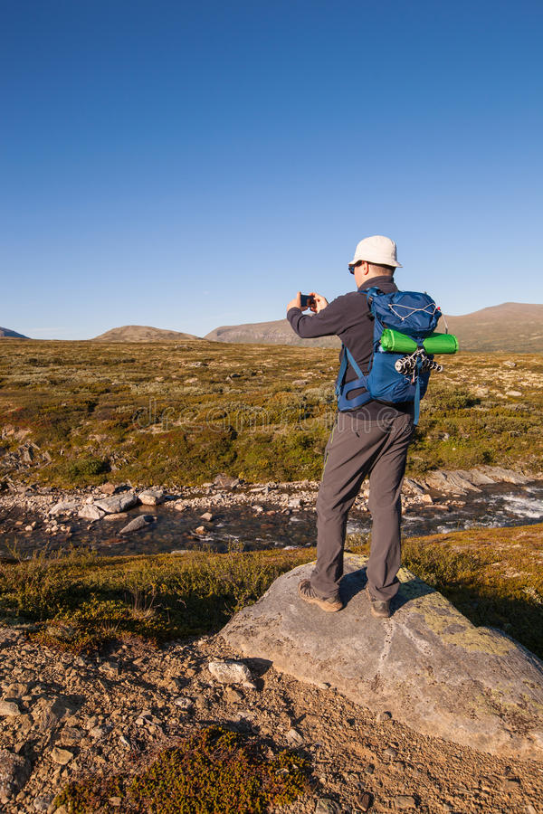 Hiker taking photo of mountain landscape with smartphone.  stock photos