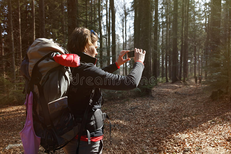Hiker taking photographs on her hike through the woods stock photos