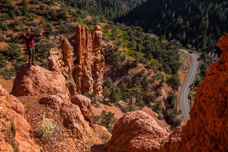 Hiker taking selfie in dangerous position near cliff edge. Southern Utah desert hiking royalty free stock images