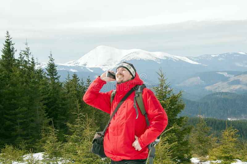 Hiker talking on the smartphone in the winter mountains stock photo