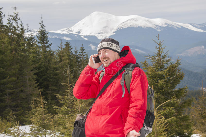 Hiker talking on the smartphone in the winter mountains royalty free stock photo