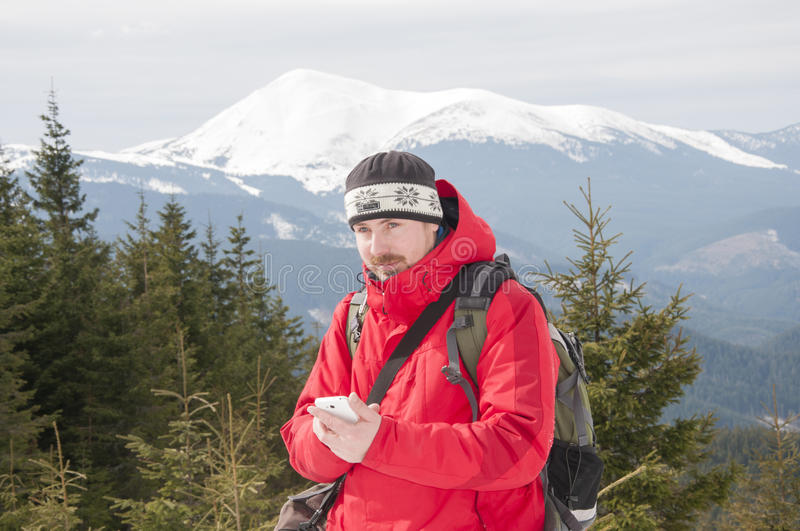 Hiker talking on the smartphone in the winter mountains stock photos