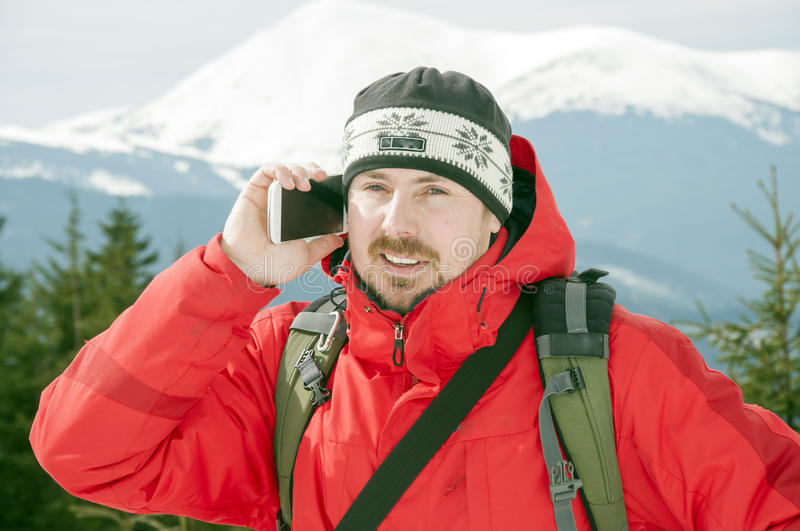 Hiker talking on the smartphone in the winter mountains stock photography