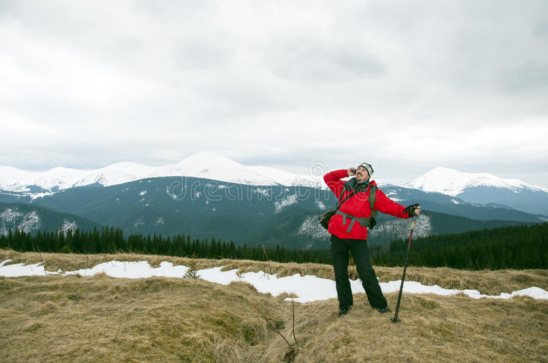 Hiker talking on the smartphone in the winter mountains stock images
