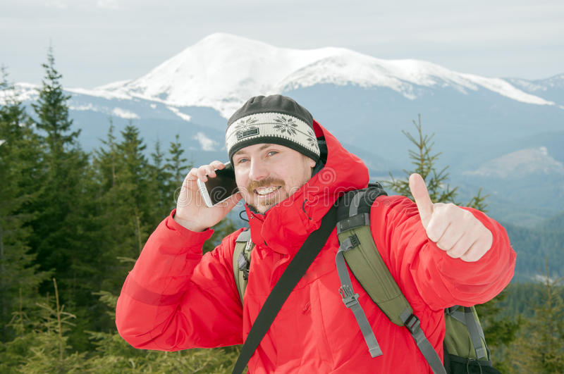 Hiker talking on the smartphone in the winter mountains royalty free stock image