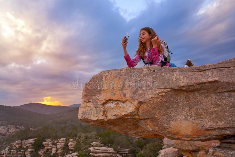 Hiker teen girl selfie phone on peak of mountain royalty free stock image