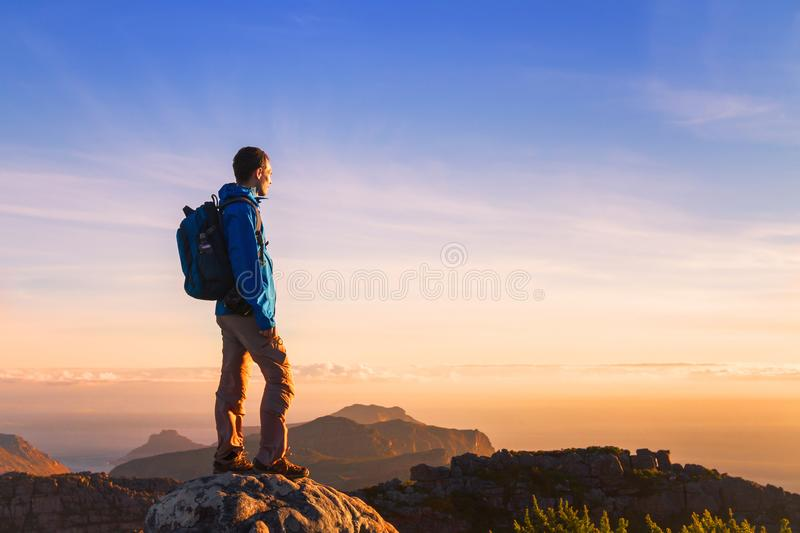 Hiker on top of the mountain enjoying sunset stock image