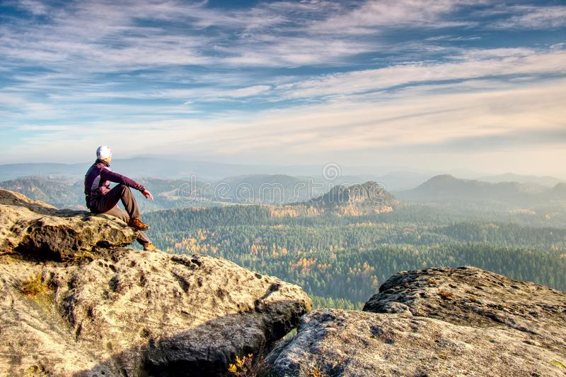 Hiker in trekking clothes sit alone on rock summit. Wonderful daybreak in mountains stock photography