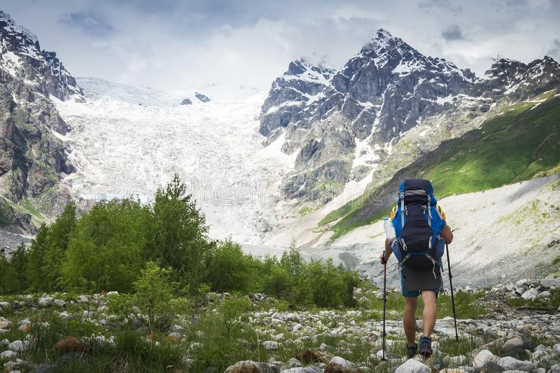 Hiker trekking in the mountains. Climber with tourist backpack goes to rocky mountain covered with snow. Leisure activity stock images
