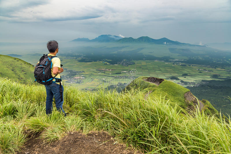 Hiker trekking to the hill top and watching mount Aso volcano. In Kumamoto stock photos