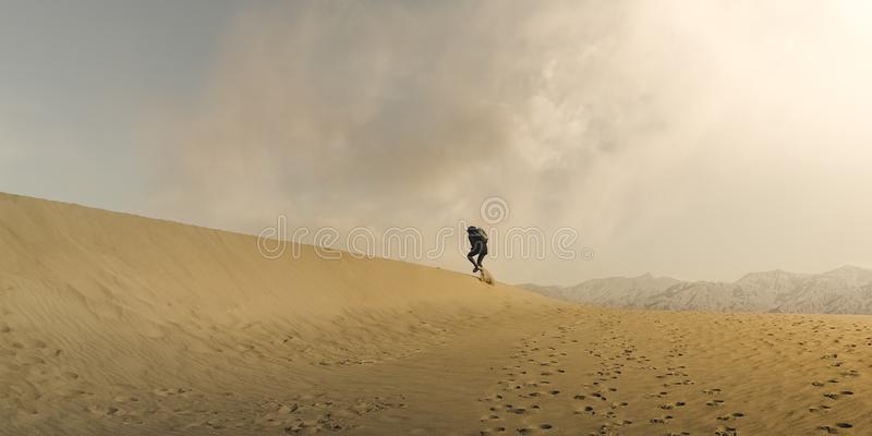Hiker Trudging through desert sand dunes in Death Valley National Park royalty free stock photos