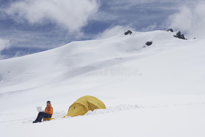 Hiker Using Laptop By Tent On Snowy Mountain Slope royalty free stock photos