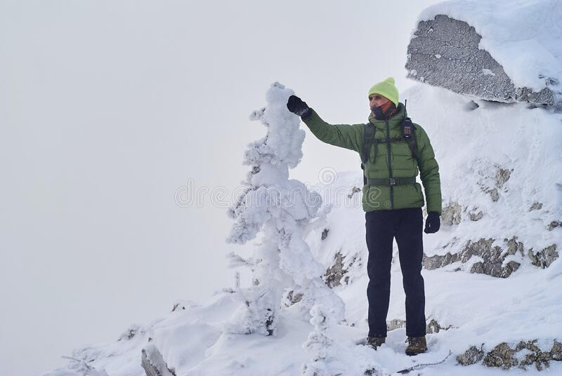 Hiker with a walkie-talkie peers into the distance, standing on top of a mountain during a snowstorm. Male hiker with a walkie-talkie anxiously peers and shows a royalty free stock images