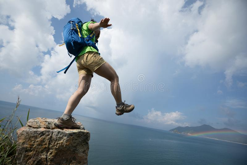 Hiker walking off cliff edge with the eyes covered. Woman walking off cliff edge with the eyes covered stock photography