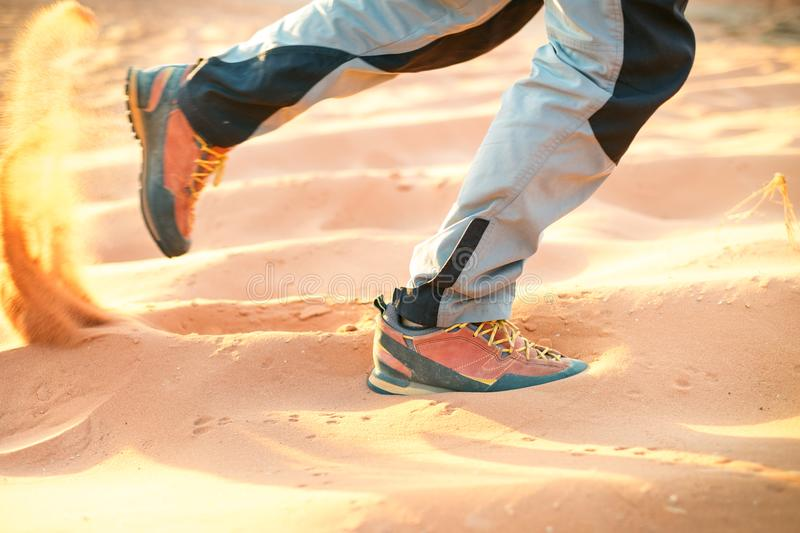 Hiker walking throught sandy desert. Traces in sand. Focus on a man legs. Tourist in a desert. Sandy background. stock photo