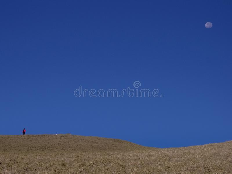 A hiker who wears a red jacket stands on the higher place of a hill. Behind him is clean sky and the moon. Good for use as backgr. Ounds royalty free stock photos