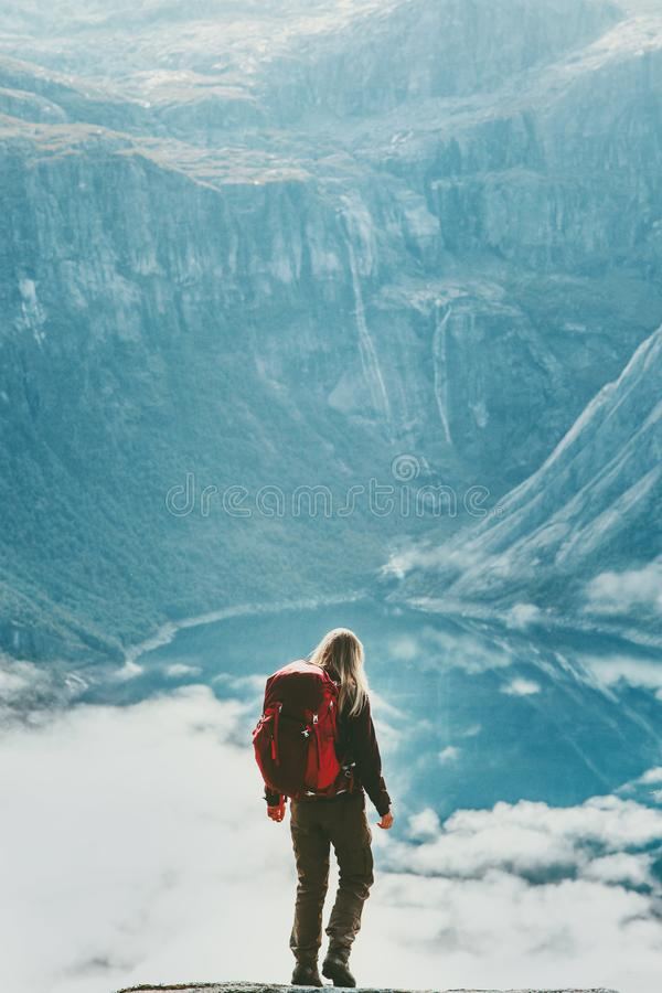 Hiker woman with backpack above clouds and lake in mountains stock photos