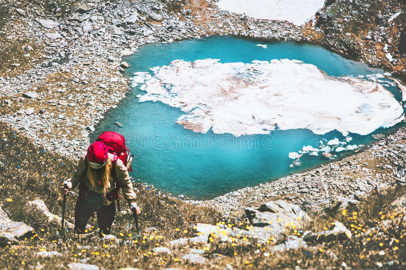 Hiker woman climbing at blue lake heart shaped. In mountains with backpack Travel Lifestyle adventure concept summer vacations outdoor active healthy life royalty free stock images