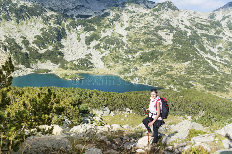 Hiker woman in a high mountain on a blue lake background royalty free stock photography