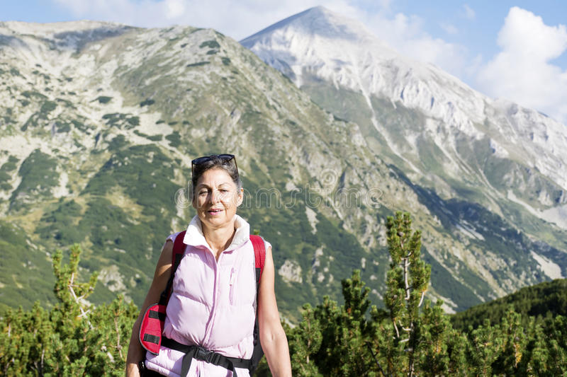 Hiker woman in a high mountain on a Vihren peak background royalty free stock photo