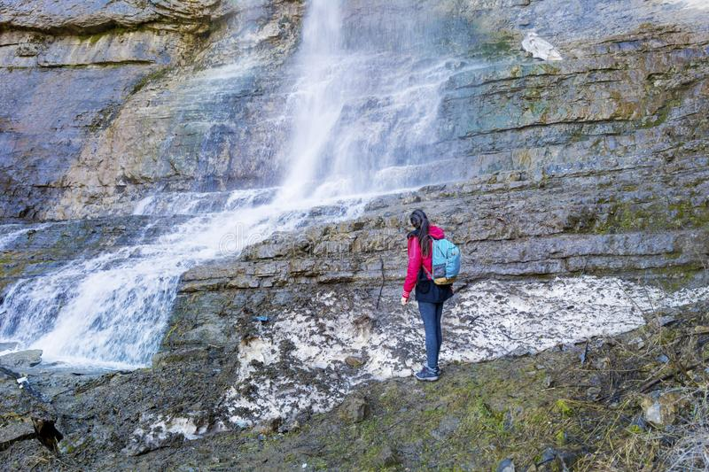 Hiker Woman Looking Big Waterfall. Happy woman enjoying the stunning view in the spring mountain with lush waterfall stock images