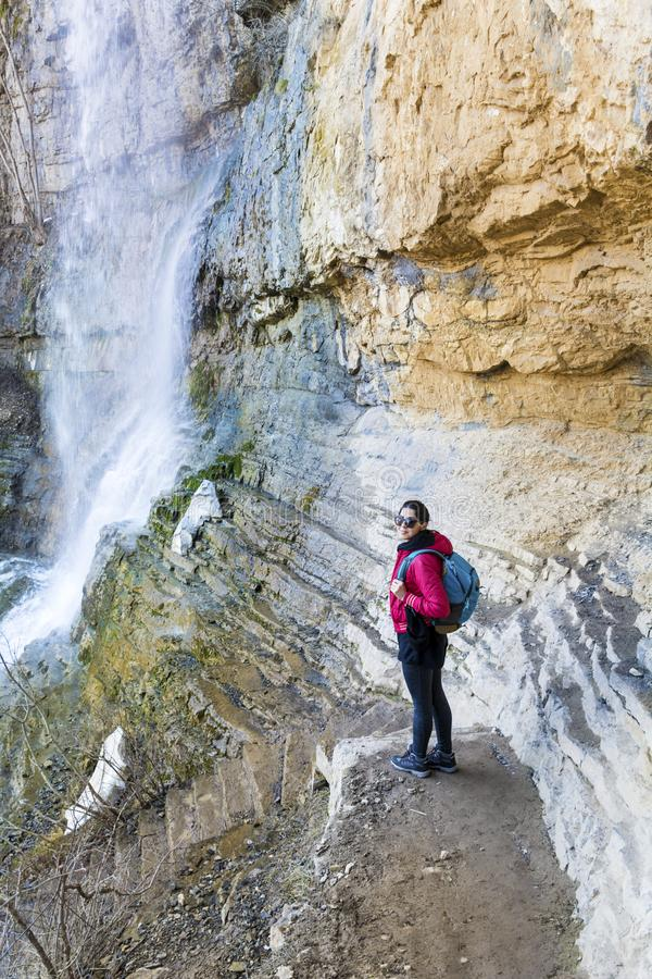 Hiker Woman Looking a Big Waterfall in the Rocks. Happy woman standing on a rocks and enjoying the stunning view in the spring mountain with lush waterfall stock photo