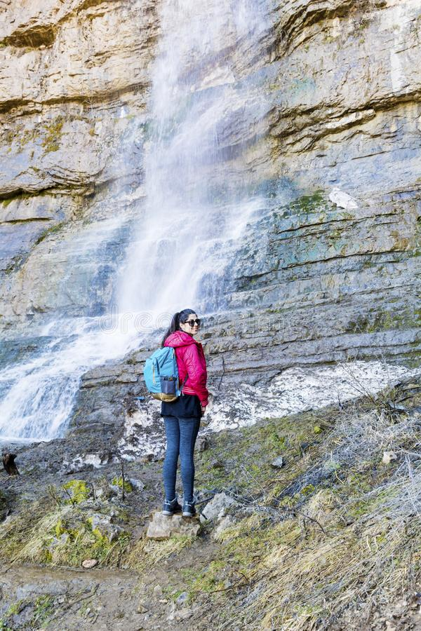 Hiker Woman Looking a Big Waterfall in the Rocks. Happy woman standing on a rocks and enjoying the stunning view in the spring mountain with lush waterfall stock images