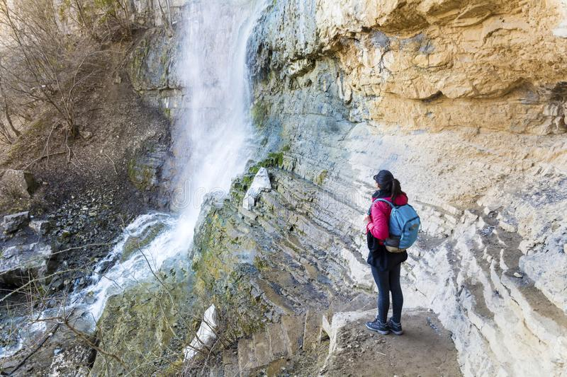 Hiker Woman Looking a Big Waterfall in the Rocks. Happy woman enjoying the stunning view in the spring mountain with lush waterfall stock photo