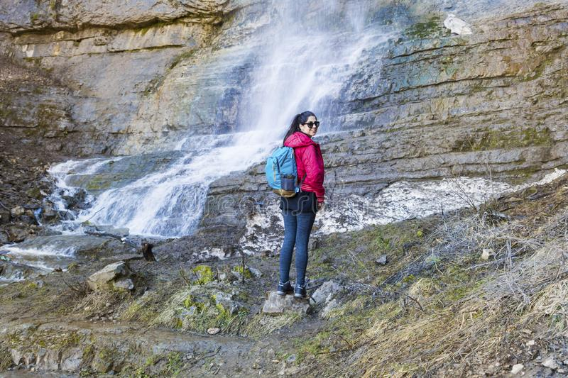 Hiker Woman Looking a Big Waterfall in the Rocks. Happy woman standing on a rocks and enjoying the stunning view in the spring mountain with lush waterfall royalty free stock photos