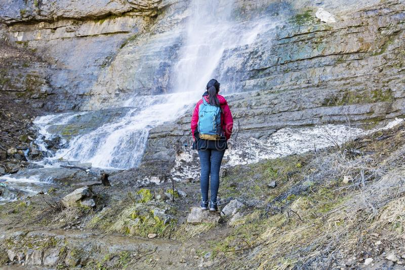 Hiker Woman Looking a Big Waterfall in the Rocks. Happy woman standing on a rocks and enjoying the stunning view in the spring mountain with lush waterfall stock photos