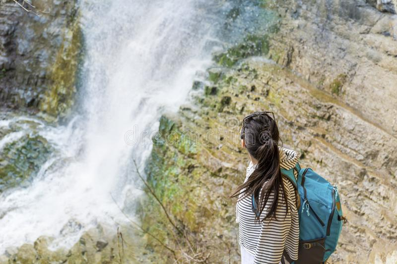 Hiker Woman Looking a Big Waterfall in the Rocks. Happy woman standing on a rocks and enjoying the stunning view in the spring mountain with lush waterfall stock image