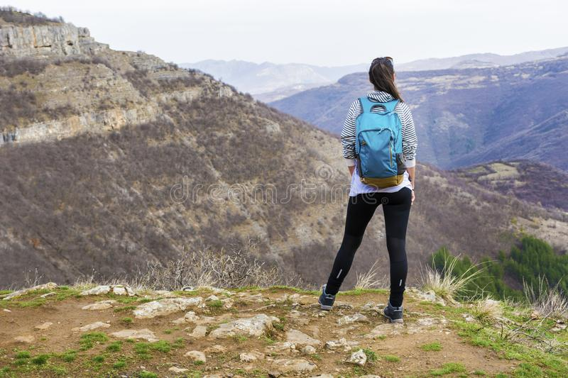 Hiker Woman Looking the Mountain View. Happy woman relaxing in a high mountain and Enjoying the Panoramic View from above .Adventure Concept royalty free stock photo
