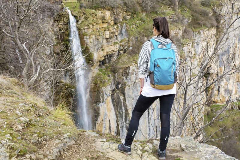 Hiker Woman Looking Waterfall in the Mountain. Happy woman relaxing in a high mountain and Enjoying the Lush Waterfall View from above .Adventure Concept stock photography