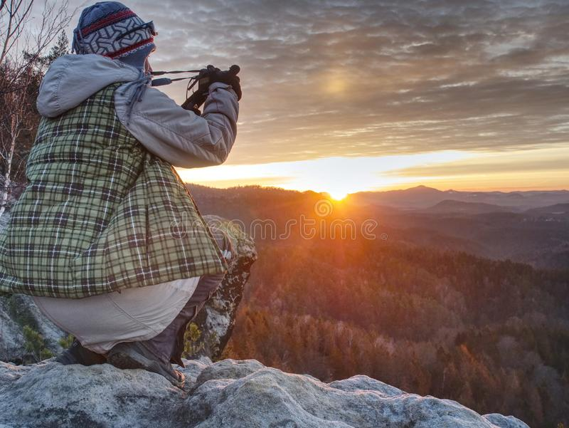 Hiker woman photographer takes photos from sharp cliff edge. Hiker woman photographer takes impresive photos from sharp cliff edge, work, wonderful, victory stock image
