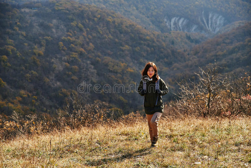 Hiker woman walking in autumn mountains stock images