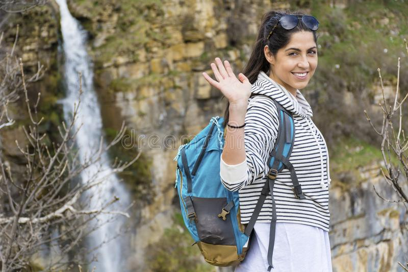 Hiker Woman on a Waterfall Background in the Mountain. Happy woman relaxing in a high mountain and Enjoying the Lush Waterfall View from above .Adventure Concept royalty free stock photos