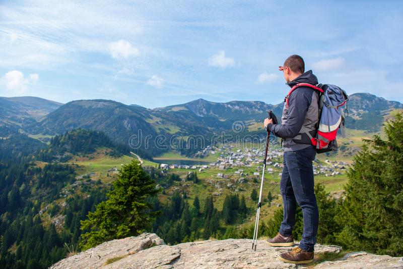Hiker young man with backpack and trekking poles standing on edge of cliff and looking at the lake, rear view royalty free stock photo