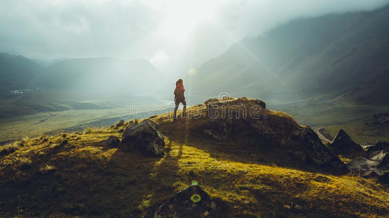Hiker Young Woman With Backpack Rises To The Mountain Top Against Backdrop Of Sunset. Discovery Travel Destination Concept. Young girl on foot hiker with a royalty free stock image